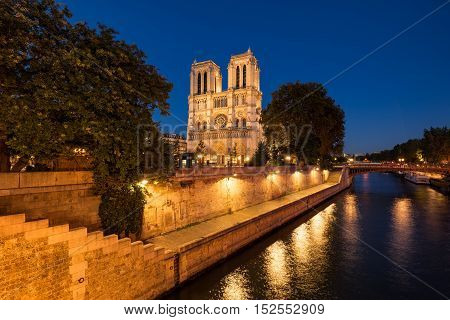 Notre Dame de Paris cathedral illuminated at twilight with the Seine River and the Pont au Double on Ile de La Cite. Summer evening in the 4th Arrondissement Paris France