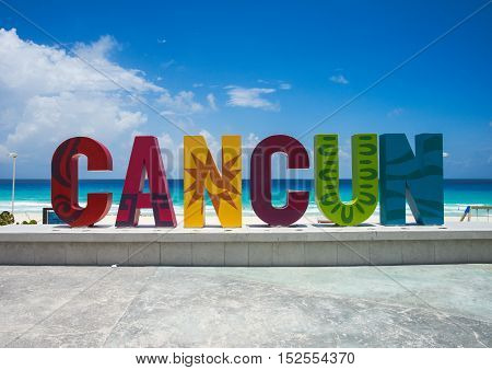 Cancun sign on a sunny day with blue water