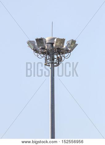 Outdoor stadium floodlight pole against daytime blue sky background