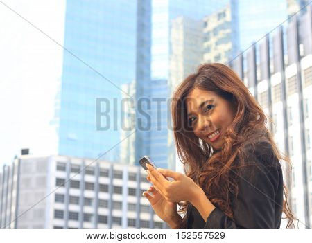 Portrait of Asian business woman on black dress use moblie with tower background