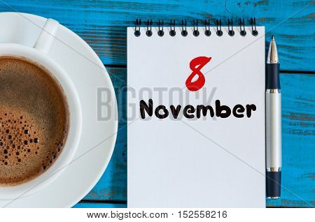 November 8th. Day 8 of month, cappuccino cup with calendar on journalist workplace background. Autumn time. Empty space for text.