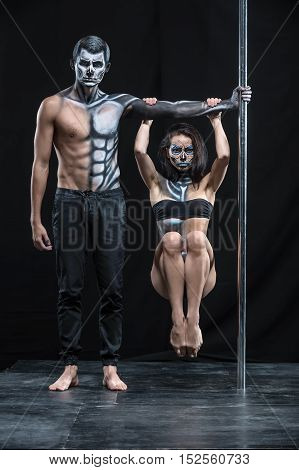 Perfect couple of pole dancers in the dark studio. Man holds a pylon with the left hand. Girl hangs with tighten knees on the guy's left arm. They wear black sportswear and have a horrific body-art.