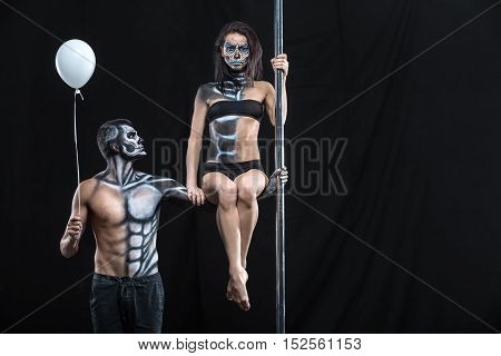 Sportive couple of pole dancers in the dark studio. Man holds a pylon with the left hand and holds a balloon in the right. Girl sits on the guy's left arm. They have a horrific body-art. Horizontal.