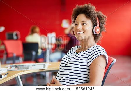 Casual portrait of a business woman at her desk and wearing headphones while in a bright and sunny startup with the team in the background