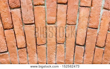 Fragment of a red brick wall with an arch. Background