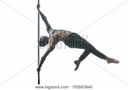 Perfect pole dancer with horrific body-art hangs horizontal on a pylon in the studio on the white background. He wears black pants. Guy holds the pylon with his stretched hands. Horizontal.