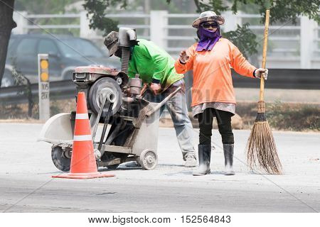Worker cutting asphalt using a cut-off saw at road construction site