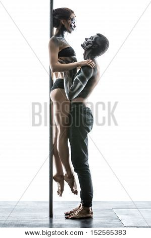 Passionate couple of pole dancers with horrific body-art in the studio on the white background. Guy holds a girl in his hands and pressing her to the pylon. They are looking at each other. Vertical.
