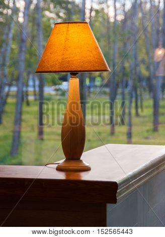 Burning table lamp in front of the window .