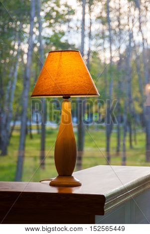 Burning table lamp in front of the window