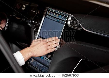Using navigation system in car, hand on display