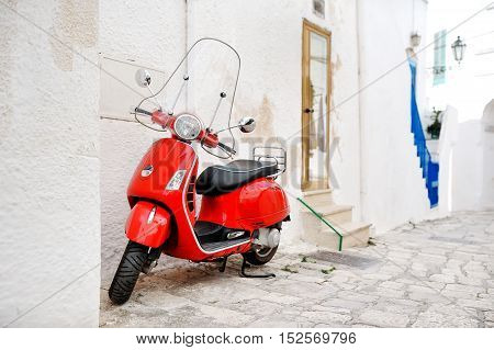 Apulia Italy - red scooter in an alleyway of the white city Ostuni
