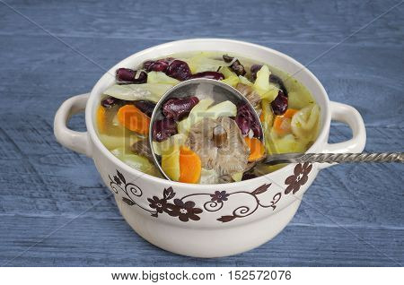Vegetable soup with red beans and mushrooms, blue wooden background