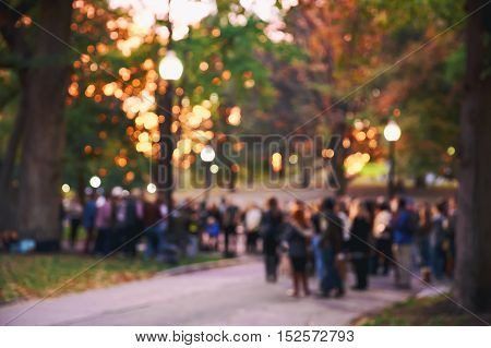 blurred background a crowd of people. a lot of people in the evening in the autumn park. concert, meeting, protest action. blurred motion