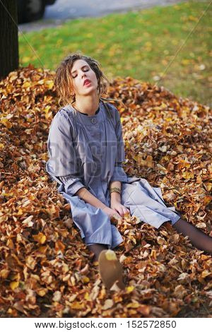 Pretty droll girl in a lilac cloak sitting on yellow autumn leaves closing his eyes and showing tongue