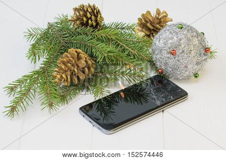 Fir Branch With Gold Cones, Toys And Mobile Phone On A Wooden Table.