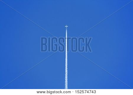 Airplane with vapor contrail in clear sky