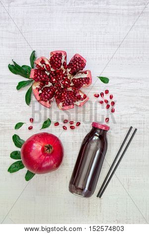 Left bottle of pomegranate juice near pomegranate, pomegranate slices, seeds on a light white wood background right empty space. Bottle of pomegranate juice and pomegranates. Vertical. Top view.