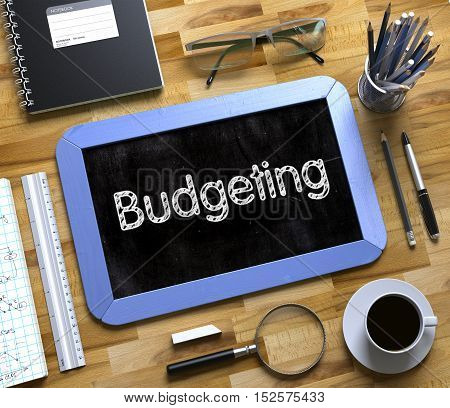 Budgeting Handwritten on Blue Chalkboard. Top View Composition with Small Chalkboard on Working Table with Office Supplies Around. Small Chalkboard with Budgeting. 3d Rendering.