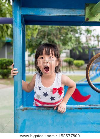 Happy asian baby child playing on playground Girl gapes in surprise looking at camera