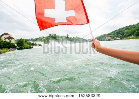 Holding a swiss flag on Rhine waterfall background in Switzerland