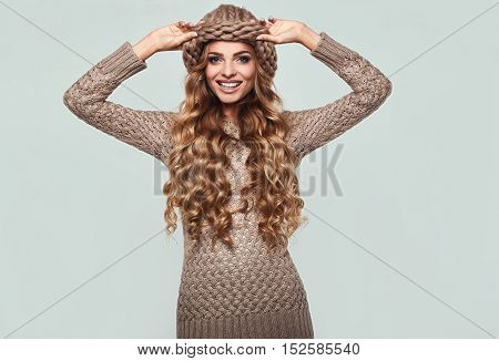 Portrait of beautiful smiling blond woman with long hair brown sweater and hat