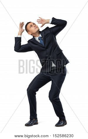 Young businessman in defensive pose afraid of something isolated on white background. Body language. Fear and fright. Business staff.