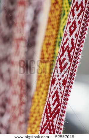 Different Latvian traditional woven folk belts with force plates
