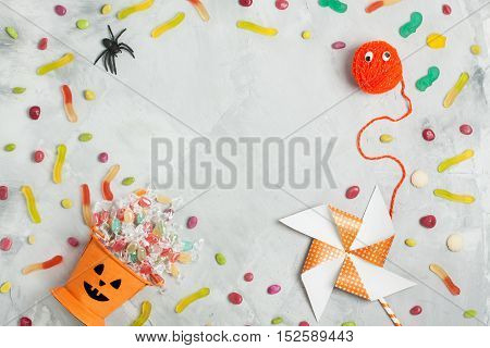 Halloween Composition With Orange Candy Bucket, Jujubes, Spider And Whirligig
