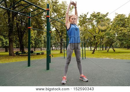 Young sportswoman stretching and preparing to gym