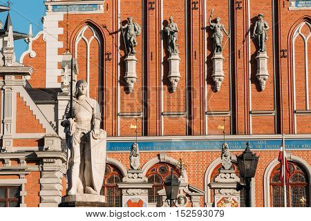Statue Of Roland At The Town Hall Square On The Background Of The House Of Blackheads In Riga, Latvia. Sunny Summer Day With Blue Sky. Famous Landmark. Old Architecture. Travel Destination