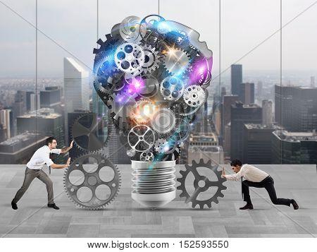 Business team push gears towards a great light bulb. build an idea concept