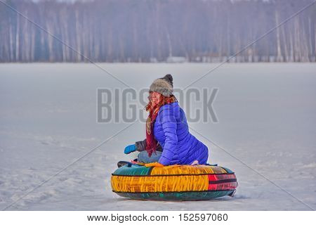 Happy young woman enjoying a winter sleigh ride on a winter slope