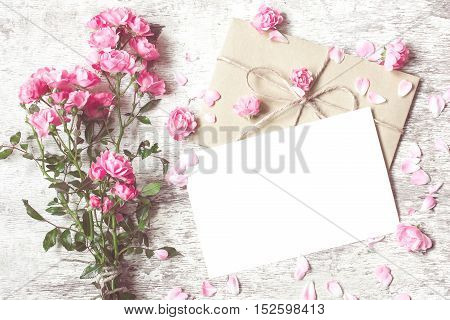 Bouquet of tender roses with a blank greeting card and envelope on white rustic wooden background with copy space. vintage toning