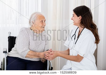 Happy Female Doctor Consoling Handicapped Senior Patient In Hospital