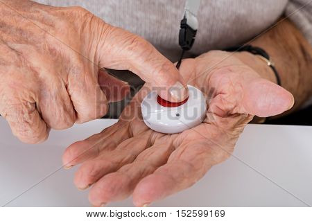 Close-up Of Senior Woman Pressing Alarm Button For Emergency