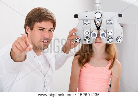 Young Male Optometrist Checking Girl's Vision With Phoropter