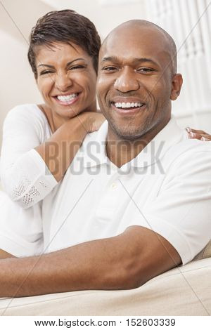 A happy smiling African American man and woman couple with perfect teeth, in their thirties sitting at home