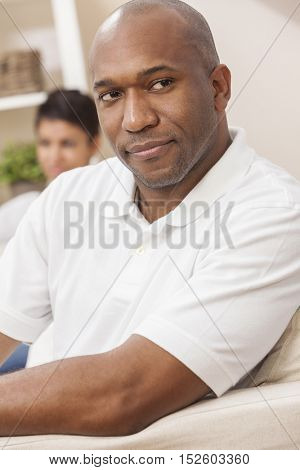 A handsome African American man sitting thoughtful at home with his girlfriend or wife behind him