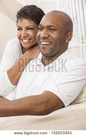 A happy African American man and woman couple with perfect teeth, in their thirties sitting at home