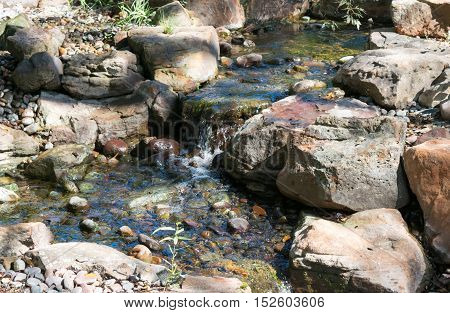 Flowing clear water feature with rocky borders