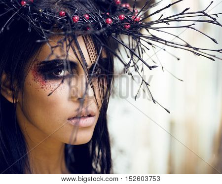 pretty brunette woman with make up like demon at halloween, dark scary look for holiday celebration close up