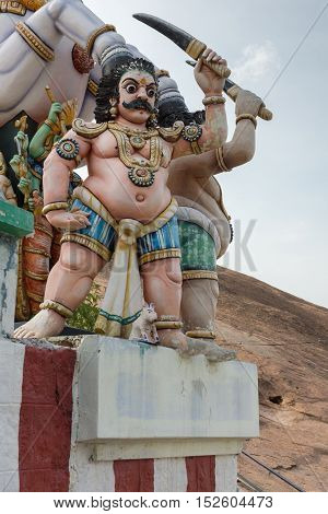 Madurai India - October 21 2013: Statue of belligerent Karuppana Sami in front of a horse. He looks hostile and swings a big knife. All colorful statues at his shrine near Nagamalai village.