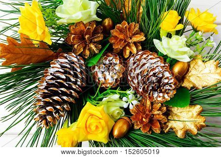 Christmas background with golden decorated pine cones and silk roses. Christmas party decoration top view.