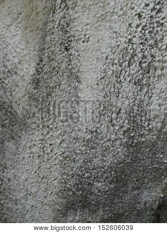 This vertical image shows close-up of weathered heavily textured stucco in shades of gray as part of a historic bridge.
