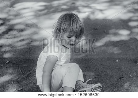 Toddler sitting and crying on the street