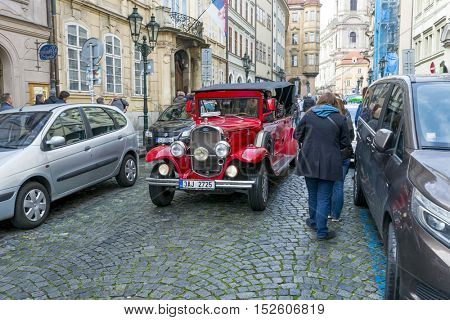 PRAGUE, OCTOBER 15: Old historic red car Praga on Mostovska street on October 15, 2016 in Prague, Czech Republic. Old cars are in Prague for tourists on tours of the city.