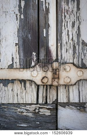 Detail of old wooden window shutters with rusty iron hinge and peeling paint. Toulouse, France.