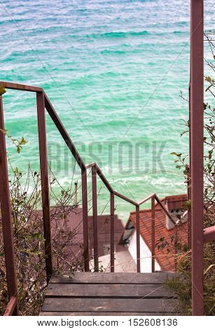 Wooden Ladder with metal handrails with ocean on the background