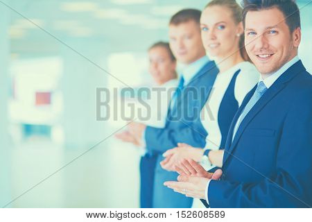 Portrait of businesspeople applauding while in a meeting at office